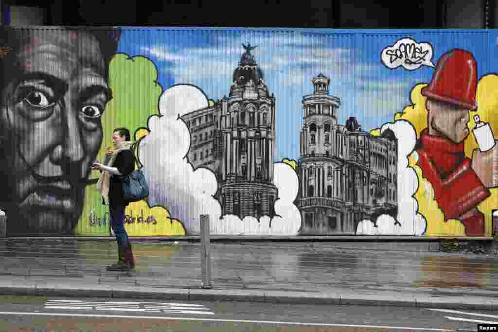 A woman smokes beside a barrier that is decorated with artwork in central Madrid, Spain.