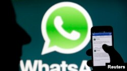 A Whatsapp App logo is seen behind a Samsung Galaxy S4 phone that is logged on to Facebook in the central Bosnian town of Zenica, February 20, 2014. Facebook Inc will buy fast-growing mobile-messaging startup WhatsApp for $19 billion in cash and stock in