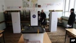 科索沃选民在首都普里什蒂纳的投票站准备投票