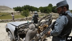 Cảnh sát Afghanistan xem xét thiệt hại của một chiếc xe sau vụ nổ bom ở thị trấn Deh Bala