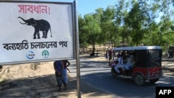 "FILE - A sign reading ""Warning! - Route for Wild Elephants"" is pictured near Balukhali camp for Rohingya refugees, in Cox's Bazar, Bangladesh, Oct. 14, 2017."
