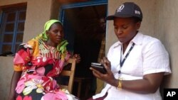 A WFP field monitor assistant conducts a food security survey with a Burundian resident in Bihogo village, using a personal digital assistant (PDA) to collect the data