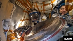NASA astronaut Jeff Williams, left, Russian cosmonaut Alexey Ovchinin of Roscosmos, center, and Russian cosmonaut Oleg Skripochka of Roscosmos are seen inside the Soyuz TMA-20M spacecraft a few moments after they landed in a remote area in Kazakhstan.