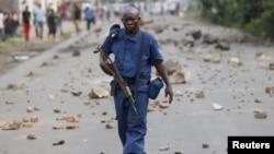 布隆迪人抗议总统恩库伦其扎竞选第三个任期时,一名手持步枪的警察走在首都布琼布拉的街头(2015年5月20日)