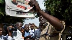 Un policier ougandais tient un journal devant des journalistes et membres du Réseau des droits de l'homme qui protestent devant le siège du journal Daily Monitor, à Kampala, Ouganda, 3 mai 2013.