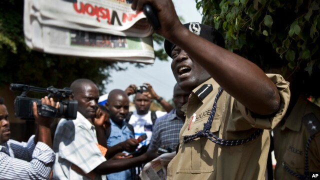 A Ugandan policeman holds up a newspaper, just before police fired tear gas to disperse the demonstration in downtown Kampala, Uganda, May 28, 2013. Some local activists are writing and distributing books that they hope can be as effective as placards.