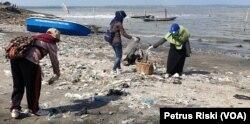 Para relawan memunguti sampah plastik yang banyak berserakan di pantai Kenjeran sisi timur Jembatan Suramadu (Foto:VOA/ Petrus Riski).