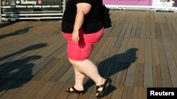 FILE - A woman walks along a boardwalk in New York. The WHO recommends people keep their sugar intake at below 10 percent of their total energy needs.