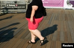 FILE - A woman walks along a boardwalk in New York.