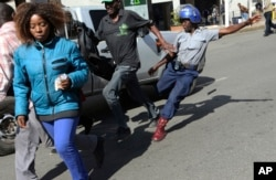 FILE: A riot police man kicks out at a man during protests in Harare, Friday, Aug. 16, 2019. The main opposition Movement For Democratic Change party is holding protests over deteriorating economic conditions in the country.