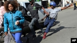 FILE: A riot police man kicks out at a man during protests in Harare, Friday, Aug. 16, 2019.