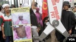 Sejumlah TKI memegang poster protes dalam demonstrasi di depan gedung DRP/MPR, terkait kasus penyiksaan Sumiati.