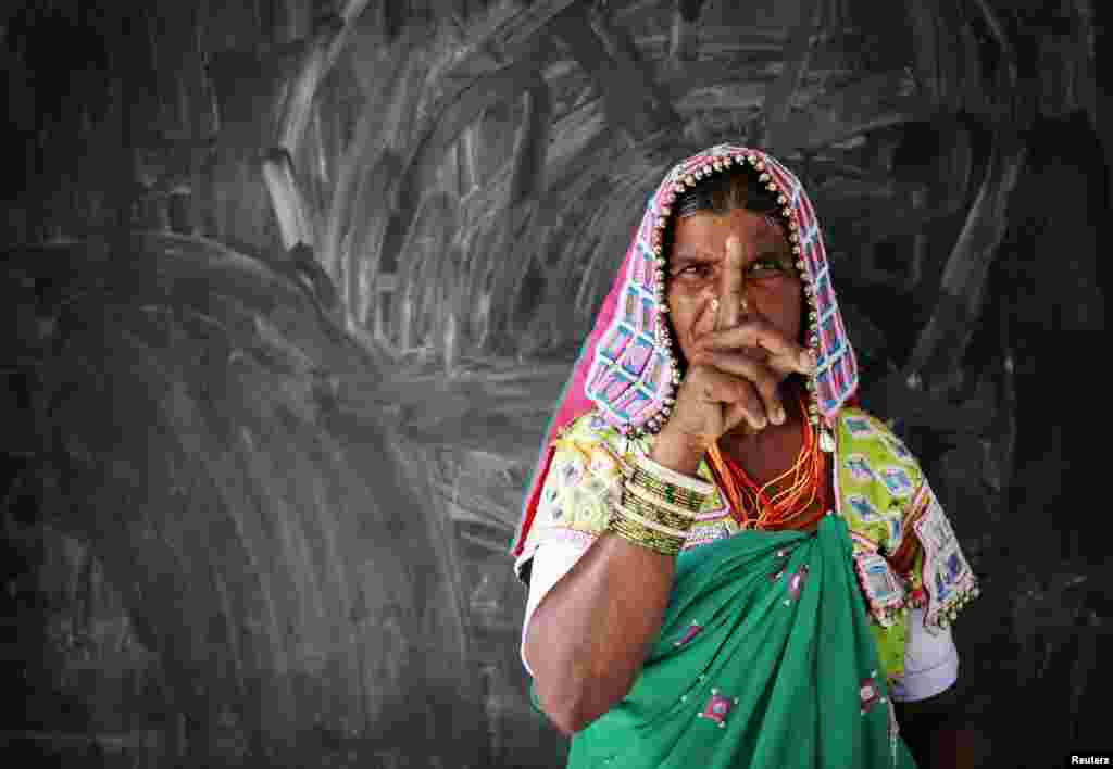 A tribal woman shows her ink-marked finger after voting at a polling center in Rangareddy district in Andhra Pradesh, India, April 30, 2014.