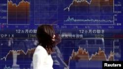 Seorang perempuan berjalan melewati papan elektronik yang menunjukkan grafik-grafik perdagangan saham di Nikkei di Tokyo, Jepang, 23 Oktober 2017. (Foto: REUTERS/Issei Kato)
