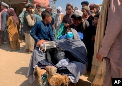 A porter pushes a wheelbarrow carrying an elderly Afghan woman with her family as they enter into Pakistan from Afghanistan at a border crossing, in Chaman, Pakistan, Thursday, Aug. 19, 2021.