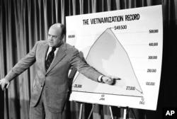ລັດຖະມົນຕີປ້ອງກັນປະເທດ ທ່ານ Melvin R. Laird, ຊີ້ມືໃສ່ຕາຕະລາງ ສະແດງໃຫ້ເຫັນສະຖິຕິ Vietnamization ຂອງລັດຖະບານ ໃນລະຫວ່າງກອງປະຊຸມຖະແຫຼງຂ່າວ. 11 ຕຸລາ 1972. ນະຄອນຫຼວງ ວໍຊິງຕັນ.