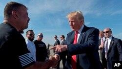 El presidente Donald Trump saluda a la gente después de que llegó al aeropuerto internacional de Palm Beach en West Palm Beach, Florida, el viernes 17 de febrero de 2017. Trump está pasando un tercer fin de semana consecutivo en su finca de Mar-a-Lago.