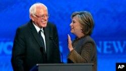 Bernie Sanders, à gauche, s'entretient avec Hillary Clinton lors du débat des candidats démocartes pour les primaires de leur parti, à l'institut Saint Anselm à Manchester, N.H., 19 décembre 2015.