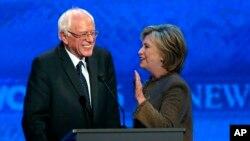 Hillary Clinton, kanan, berbicara pada Bernie Sanders di sela-sela waktu istirahat pada debat calon presiden dari Partai Demokrat, di Saint Anselm College, Manchester, N.H., 19 Desember 2015.