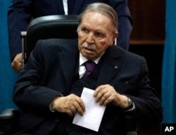 FILE - Algerian President Abdelaziz Bouteflika prepares to vote in Algiers, May 4, 2017.