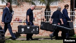 Members of the Australian Federal Police (AFP) forensic unit carry equipment into a house that was involved in pre-dawn raids in the western Sydney suburb of Guilford, September 18, 2014.