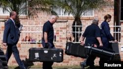 Petugas forensik kepolisian Australia membawa peralatan ke dalam rumah yang digerebek di Sydney, terkait dugaan terorisme (18/9). (Reuters/David Gray)