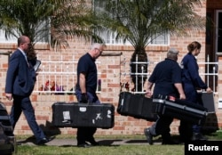"""FILE - Members of the Australian Federal Police (AFP) forensic unit carry equipment into a house that was involved in pre-dawn raids in the western Sydney suburb of Guilford, Sept. 18, 2014. Without referring to specifics, Prime Minister Tony Abbott said Australia was at """"serious risk from a terrorist attack."""""""