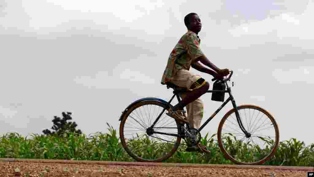 A youth rides past a bicycle along Anka-Sokoto road in northeastern state of Zamfara August 13, 2013.