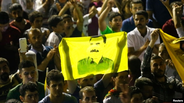 Supporters hold a flag with the image of Abdullah Ocalan, jailed leader of the Kurdistan Workers' Party (PKK) as they celebrate outside the pro-Kurdish Peoples' Democratic Party (HDP) headquarters in Diyarbakir, Turkey, June 7, 2015.