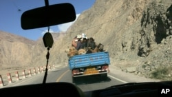 FILE - Ethnic Uighurs and camels ride together in the back of a truck along the Karakoram Highway from Kashgar towards Karakul lake in Chinas Xinjiang autonomous region, May 22. 2006.