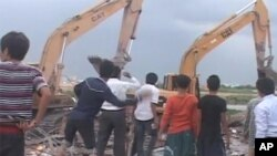 A photo taken from a Reuters video shows villagers throwing stones at excavators brought in to demolish homes at Phnom Penh's Boeng Kak lake on Friday, September 16, 2011.