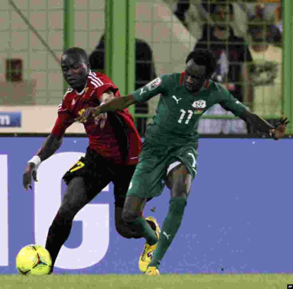 Jonathan Pitroipa, do Burkina Fasso, disputa a bola com Mateus Galiano, durante o primeiro jogo das Palancas Negras, no CAN 2012, no Estádio de Malabo, a 22 de Janeiro