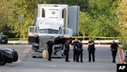 San Antonio police officers investigate the scene Sunday, July 23, 2017, where eight people were found dead in a tractor-trailer loaded with at least 30 others outside a Walmart store in stifling summer heat in what police are calling a horrific human tra