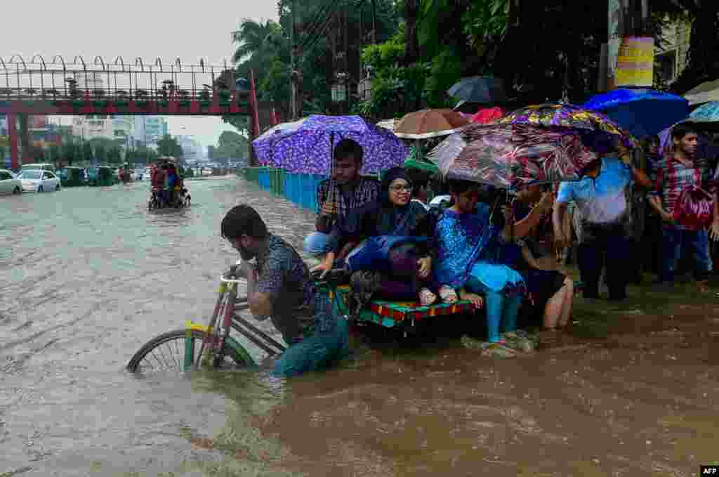Commuters use a rickshaw to cross a flooded street amid heavy rainfall in Dhaka, Bangladesh.