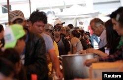 Los migrantes centroamericanos que se desplazan en una caravana a través de México hacen cola para comprar comida en un refugio que les abrió la iglesia católica, en Puebla, México, el 6 de abril de 2018.