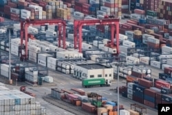 A cargo truck drives amid stacked shipping containers at the Yangshan port in Shanghai, Thursday, March 29, 2018. China's Commerce Ministry called on Washington on Thursday to discard planned tariffs.
