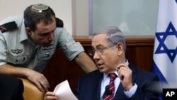 以色列总理内塔尼亚胡(右)在耶路撒冷的每周内阁会议上与他的军事秘书托莱达诺准将交谈。 (2015年10月25日)