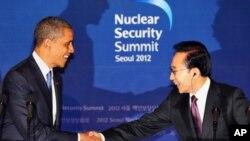 25일 한국 청와대에서 서울 핵안보 정상회의를 위해 방한한 바락 오바마(좌) 미국 대통령과 악수를 나누는 이명박(우) 한국 대통령