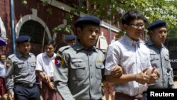 «وا لون» (راست) و «کیا سو او» (پشت سر) دو خبرنگار رویترز در محاصره ماموران نظامی