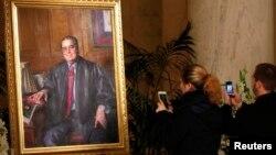 تصویر نقاشی شده از قاضی اسکالیا که دو نفر از آن عکس می گیرند