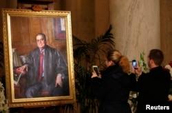 ຊາຍ, ຍິງຄູ່ໜຶ່ງຖ່າຍຮູບທາສີຂອງຜູ້ພິພາກສາສານສູງສຸດ ສະຫະລັດ ທ່ານ Antonin Scalia ທີ່ໄດ້ລ່ວງລັບໄປ ໃນຫ້ອງໃຫຍ່ຂອງສານສູງສູດໃນນະ ຄອນຫຼວງ ວໍຊິງຕັນ. 19 ກຸມພາ 2016.