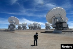 FILE - A member of the media takes pictures of the parabolic antennas of the ALMA (Atacama Large Millimetre/Submillimetre Array) project at the El Llano de Chajnantor in the Atacama desert, some 1,730 km (1,074 miles) north of Santiago and 5,000 meters above sea level, March 12, 2013.