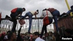 Sinh viên leo lên hàng rào của Đại học Sư phạm Quốc gia trong 1 cuộc biểu tình chống lại kết quả bầu cử tổng thống ở Tegucigalpa, 27/11/2013