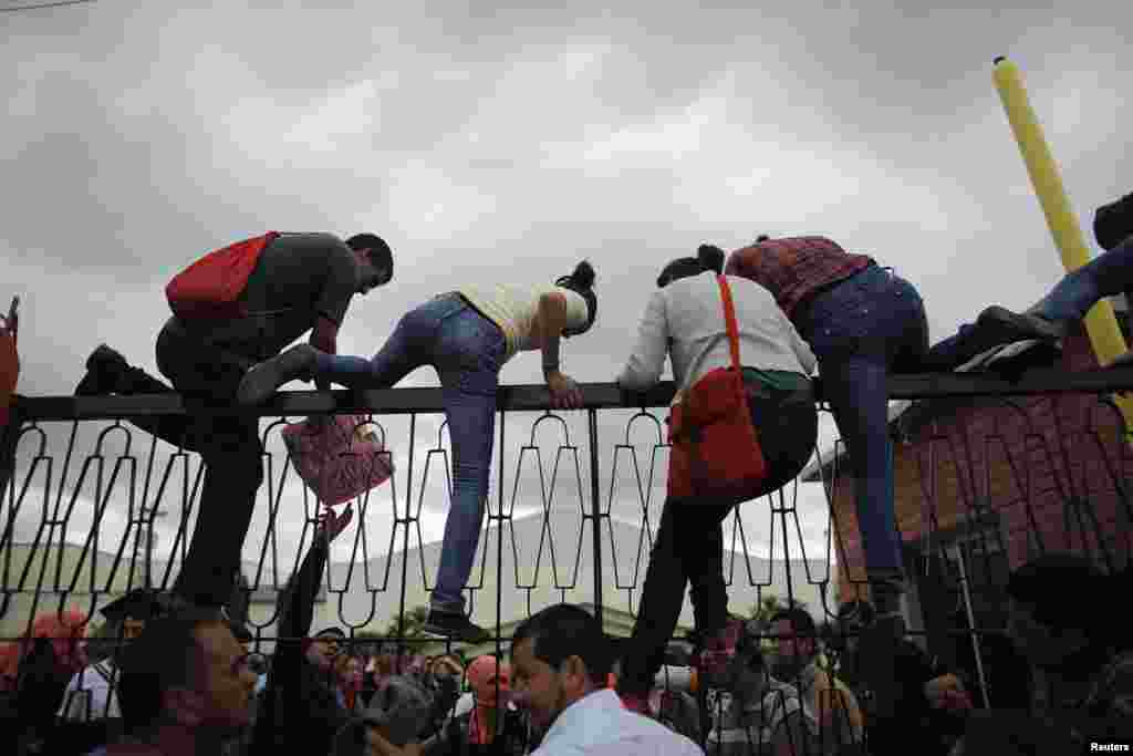 Students climb the fence of the National Pedagogical University during a protest against Sunday's presidential election results in Tegucigalpa November 27, 2013.