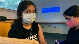 Maya Huber (kiri) turut serta dalam uji coba pemberian vaksin COVID-19 Pfizer untuk anak-anak di Universitas Rutgers di New Brunswick, New Jersey, pada 14 Juni 2021. (Foto: Nisha Gandhi via AP)