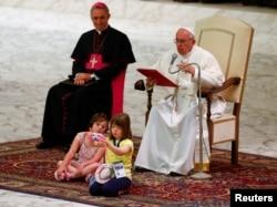 天主教教宗方济各在梵蒂冈。有儿童在他前面自拍(2016年6月11日)