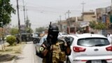 A member of the Iraqi Special Operations Forces stands guard during an intensive security deployment in Baghdad's Amiriya district, June 18, 2014.