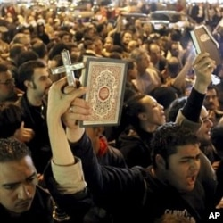 Egyptian Muslims and Christians raise a copy of the Quran and a Cross in Shubra district, Cairo, Egypt, Saturday, Jan.1, 2011 to protest against the terrorist attack on a Coptic Christian church in the northern Egyptian city of Alexandria.