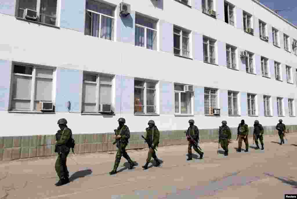 Armed men, believed to be Russian servicemen, walk on the territory of the naval headquarters in Sevastopol, Crimea, March 19, 2014.