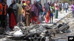 Somalis stand over the wreckage of car bomb which exploded outside a restaurant in Mogadishu, Somalia, April , 21, 2015.